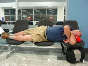 fat man sleeping in airport