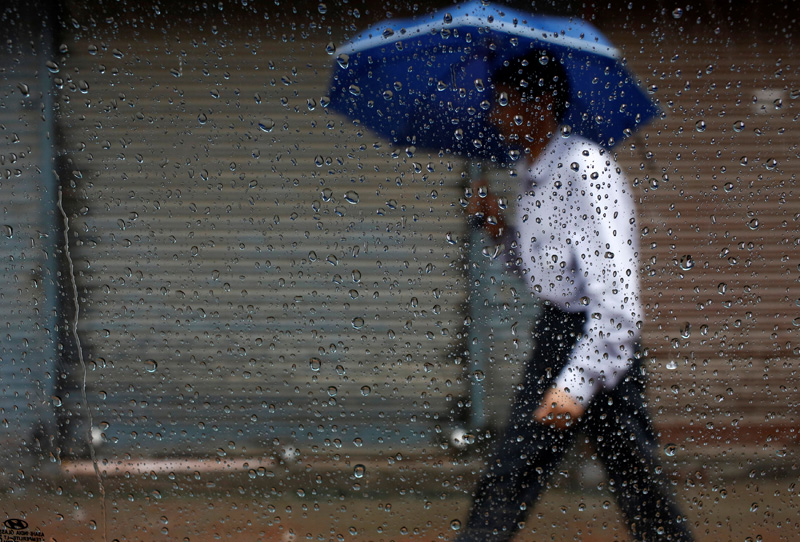 Raindrops are pictured on the window of a car as a man holding an umbrella passes by during the rainfall in Kathmandu